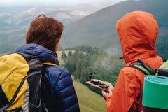 Люди используя компас в горе Стоковые Фото