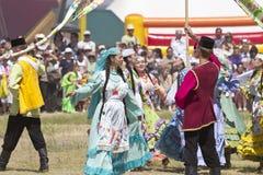 Люди и женщины в национальных костюмах танцуют традиционные народные танцы Стоковая Фотография RF
