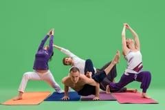 Люди и женщины делают йогу в предпосылке зеленого цвета студии Стоковое фото RF