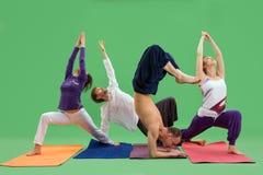 Люди и женщины делают йогу в предпосылке зеленого цвета студии Стоковые Фотографии RF