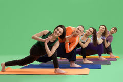 Люди и женщины делают йогу в предпосылке зеленого цвета студии Стоковое Изображение