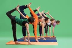 Люди и женщины делают йогу в предпосылке зеленого цвета студии Стоковая Фотография RF