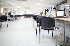 Люди и женщины работают на компьютерах в офисе автосалона Стоковое Фото