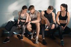 Люди и женщины сидя на стенде после тренировки в спортзале Стоковые Фотографии RF