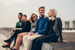 Люди и женщины сидя совместно на крыше Стоковые Фотографии RF