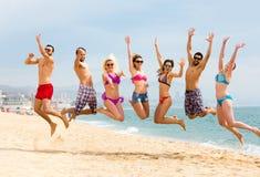 Люди и женщины скача на пляж Стоковое фото RF