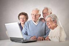 Люди и женщины смотря компьтер-книжку Стоковое Изображение