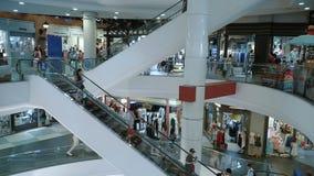 Люди идут вниз с эскалатора на моле сток-видео