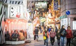 Люди идут вокруг улицы еды за башней Tsutenkaku Стоковое Изображение RF