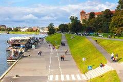Люди идут вдоль банка Рекы Висла в историческом центре города Кракова, Польше Стоковое Изображение RF