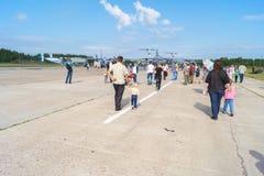 Люди идут между самолетами на дне открытых дверей на аэродроме Стоковое Фото