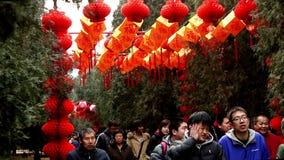 Люди идут под красные фонарики на виске Ditan справедливо во время фестиваля весны в Пекине, Китае акции видеоматериалы