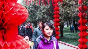 Люди идут под красные фонарики на виске Ditan справедливо во время фестиваля весны в Пекине, China1 сток-видео