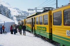 Люди идут платформой Wengernalpbahn железнодорожной в Grindelwald, Швейцарии Стоковое Изображение