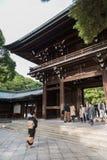 Люди идут через деревянное синто Meiji святыни в Shibuya Японии стоковые изображения