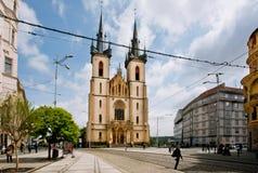 Люди идут через дорогу напротив исторической церков стоковые фото