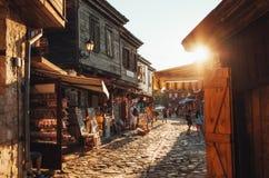 Люди идут через улицы старое nesebar на заходе солнца стоковые фото