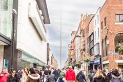 Люди идя в улицу Генри с шпилем на предпосылке стоковые изображения