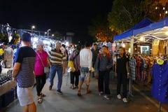 Люди идя и ходя по магазинам на рынке ночи Стоковые Изображения