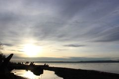 Люди идя на пляж на заходе солнца стоковые изображения