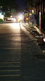 Люди идя на улицу на тени отливки ночи Стоковая Фотография