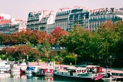 Люди идя около шлюпок и зданий в Париже, Франции стоковые изображения
