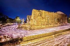 Люди идя с освещенными свечами вокруг древнего храма, Cand Стоковое Изображение