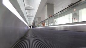 Люди и travolator внутри места ожидания в международном аэропорте сток-видео