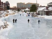 Люди катаются на коньках на раннем вечере на замороженном озере Стоковое фото RF