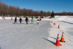 Люди катаясь на коньках на катке катания на коньках озера бобр Стоковые Изображения