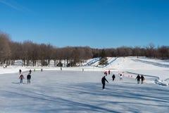 Люди катаясь на коньках на катке катания на коньках озера бобр Стоковое Изображение