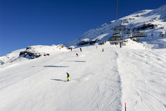 Люди катаясь на лыжах и идя вверх гора подвесным подъемником Стоковая Фотография RF