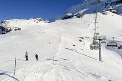 Люди катаясь на лыжах и идя вверх гора подвесным подъемником Стоковое Изображение