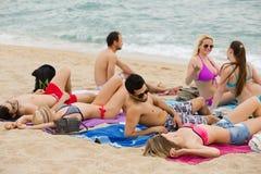 Люди кладя на песок на пляже Стоковые Фотографии RF
