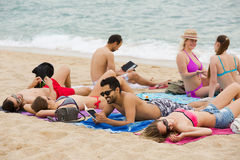 Люди кладя на песок на пляже Стоковые Изображения RF