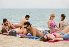 Люди кладя на песок на пляже Стоковые Изображения