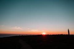 Люди наблюдая заход солнца около океана, Португалии Стоковая Фотография RF