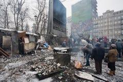 Люди нагревая огнем около баррикад после боев с полицией на сломленной улице Киева во время антипровительственного бунта стоковое фото