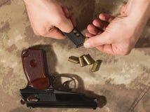Люди нагружают боеприпасы в пистолете Makarov зажима Стоковая Фотография RF