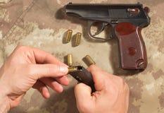 Люди нагружают боеприпасы в пистолете Makarov зажима Стоковые Изображения