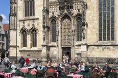 Люди наслаждаются едой и выпиваются на кафе тротуара Стоковая Фотография RF
