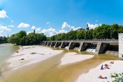 Люди наслаждаются солнечной жаркой погодой на речных берегах реки Изара в Мюнхене Стоковое Изображение RF