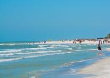 Люди наслаждаясь белым песчаным пляжем на острове сокровища приставают к берегу на Мексиканском заливе, Флориде Стоковые Фотографии RF
