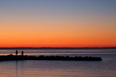 Люди наслаждаясь заходом солнца берега озера Стоковая Фотография RF