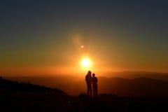 Люди наслаждаясь заходом солнца в горах Стоковое Фото