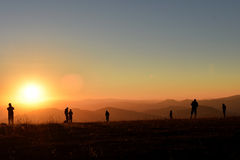 Люди наслаждаясь заходом солнца в горах Стоковое Изображение