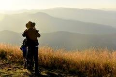 Люди наслаждаясь заходом солнца в горах Стоковые Фото