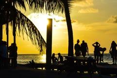 Люди наслаждаясь карибским заходом солнца, разделением, чеканщиком Caye, Белизом стоковая фотография