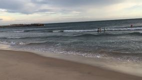 Люди наслаждаясь на пляже на заходе солнца акции видеоматериалы