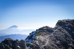 Люди на остатках Kitadake пиковых принимая и смотреть Mt fuji Стоковые Изображения RF